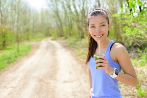 Healthy woman drinking green smoothie wearing smartwatch. Female runner resting drinking a spinach and vegetable smoothie using smart watch heart rate monitor during outdoor running workout in forest.