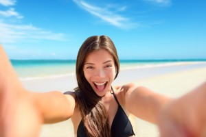 Selfie fun woman taking photo at beach vacation. Summer holiday girl happy at smartphone camera taking self-portrait on her travel vacations on pristine paradise beach.