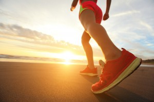 Maintain Energy During Workout - Woman Runner feet running on the beach at sunrise closeup on shoe. woman fitness sunrise jog workout welness concept. asian ** Note: Shallow depth of field