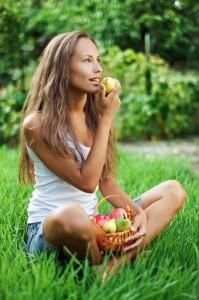 Beautiful girl eating pear on the green grass