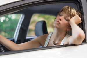 Undermethylation Symptoms - Attractive blonde young woman sleeping in a car stuck in traffic in a sunny day