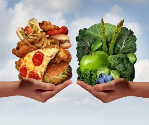 Foods NOT to eat when trying to lose weight - Nutrition choice and diet decision concept and eating choices dilemma between healthy good fresh fruit and vegetables or greasy cholesterol rich fast food with two hands holding food trying to decide what to eat.