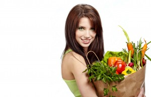 woman holding a grocery bag full of fresh and healthy food isolated on white background