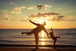 Time Management Techniques Father and son playing on the beach at the sunset time. Concept of friendly family.