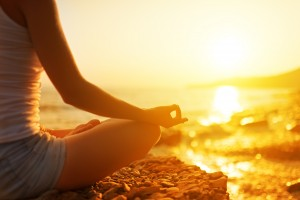The Miracle Morning Hal Elrod - hand of a woman meditating in a yoga pose on the beach