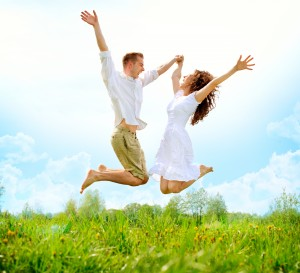 Naturopath Melbourne - Happy Couple Outdoor. Jumping Family on Green Field. Freedom concept. Free. Jumping People. Fun