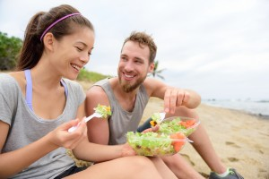 Ways to Maintain a Healthy Weight - Happy young people eating healthy salad for lunch. Multiracial group having a break on beach snacking on a vegan takeaway meal of green veggies and carrots laughing together. Casual lifestyle.
