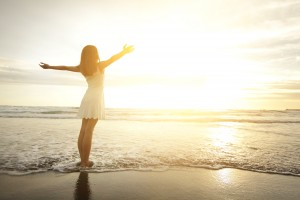 Naturopath Melbourne - Smile Freedom and happiness woman on beach. She is enjoying serene ocean nature during travel holidays vacation outdoors. asian beauty