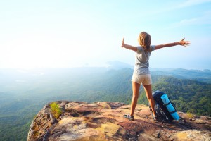 Mental Health Holistic Approach - Young happy woman with backpack standing on a rock with raised hands and looking to a valley below
