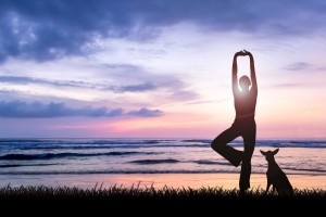 Naturopath Melbourne - Silhouette of young woman practising yoga being one perfect harmony with nature facing ocean on sunset with her dog