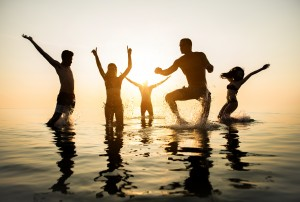 Adding Fun To Your Day - Group of happy friends jumping in to water at sunset - Silhouettes of active people dancing and having fun on the beach on vacation